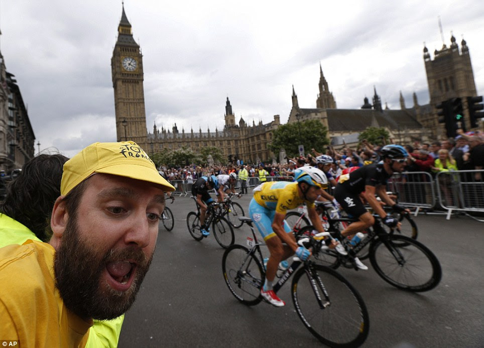 Encouragement: A cycling fan celebrates as the pack passes the Houses of Parliament in central London, during the third stage of the Tour de France race