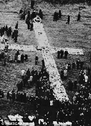 In memory: Mourners gather at a huge cross of flowers on the hillside during the funeral of the victims, left, and right, a couple lays flowers at a grave in the Aberfan Cemetery, where victims of the disaster are buried
