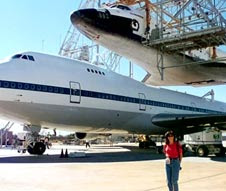 Nicole Stott with space shuttle Endeavour aboard the carrier aircraft in the background.