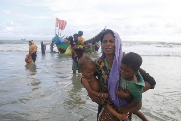 Rohingya people alight from a boat as they arrive at Shahparir Dip in Teknaf, Bangladesh. Credit: IPS