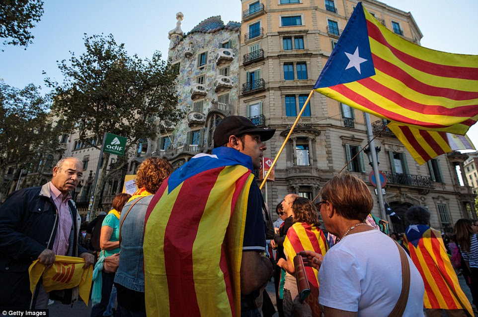 Protesters gather in the city center to demonstrate against the Spanish federal government's move to suspend Catalonian autonomy