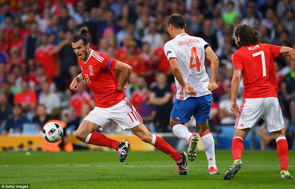 Former Tottenham Hotspur star Bale (left) goes down under the challenge of Russia's 36-year-old defenderSergei Ignashevich (No 4)