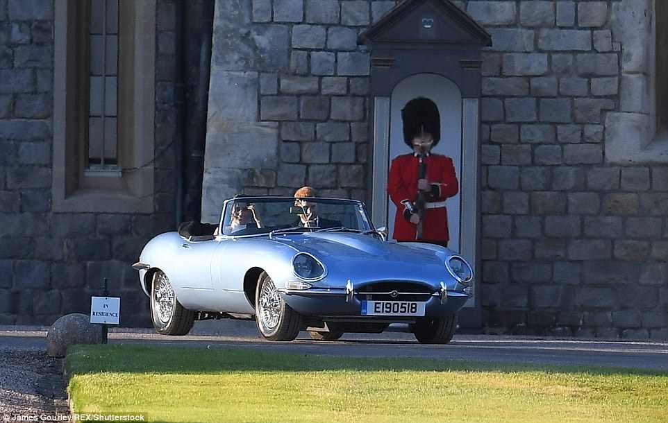 Meghan sonríe mientras su nuevo marido la conduce más allá de un guardia en el auto descapotable frente al Castillo de Windsor