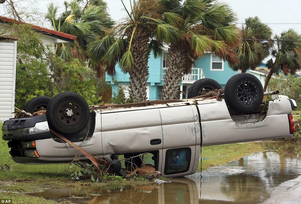 Un camion est retourné après que l'ouragan Harvey ait atterri dans la région de Coast Bend samedi, à Port Aransas, au Texas. Il n'est pas clair si le chien couché dans la voiture est mort ou blessé
