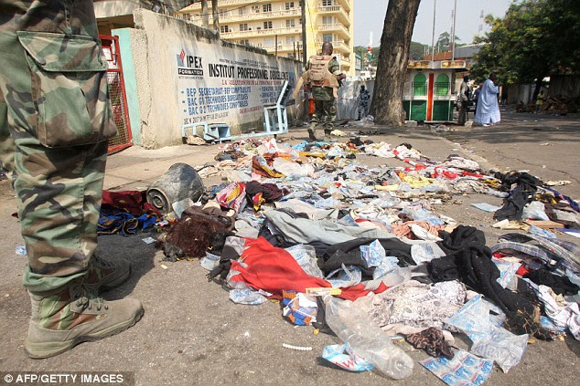 Carnage: Guards stand next to clothing and other items strewn on the ground after the stampede outside the Felix Houphouet Boigny Stadium