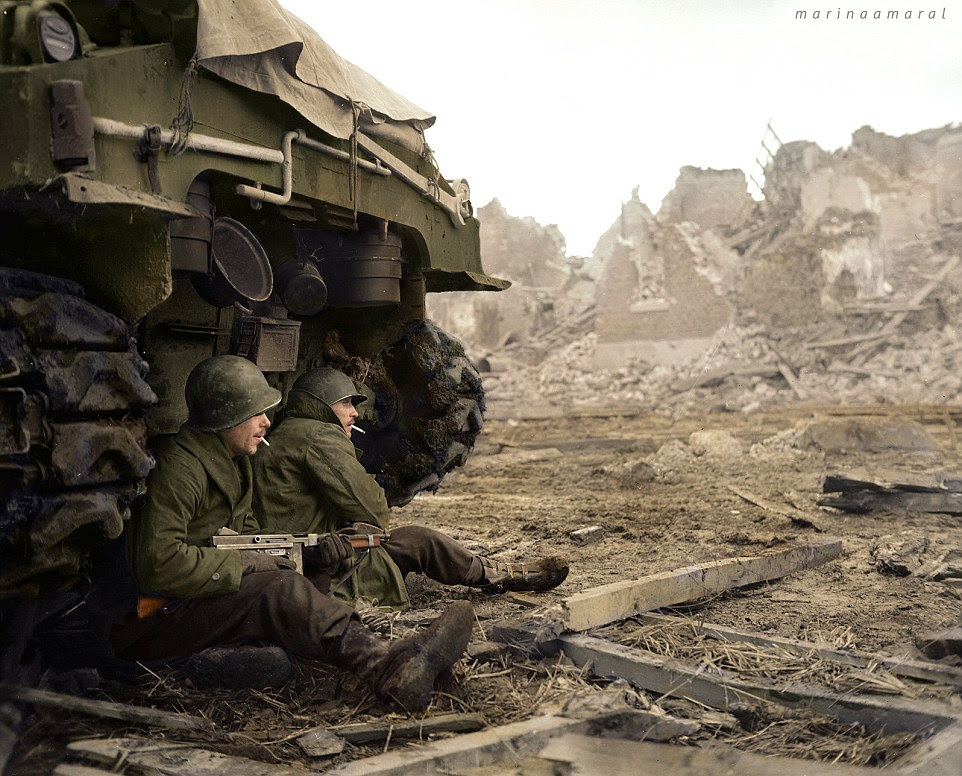 Taking shelter: Soldiers from the  36th Armoured Infantry Regiment, 9th Infantry Division at Geich, in Germany, on 11 December 1944, sit beside a tank. The 9th Infantry Division was among the first U.S. combat units to engage in offensive ground operations during World War II