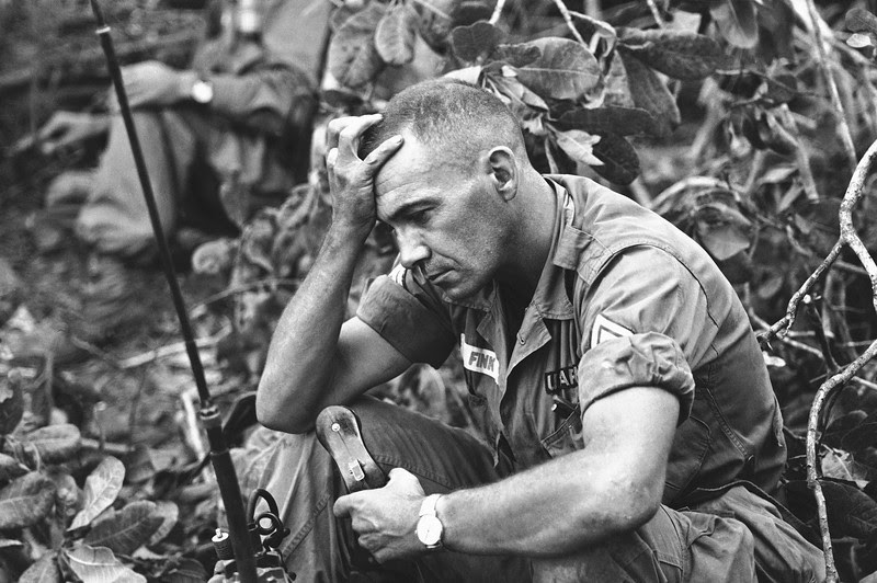 Description of  The strain of battle for Dong Xoai is shown on the face of U.S. Army Sgt. Philip Fink, an advisor to the 52nd Vietnamese Ranger battalion, shown June 12, 1965. The unit bore the brunt of recapturing the jungle outpost from the Viet Cong. (AP Photo/Steve Stibbens)