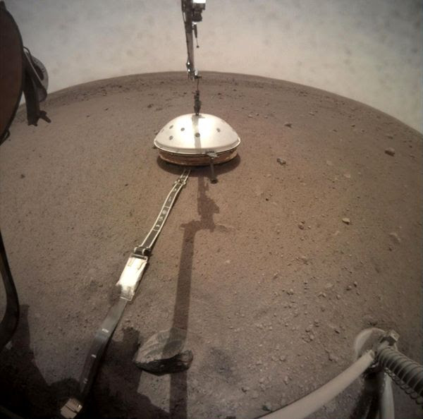 The Wind and Thermal Shield dome is placed atop the seismometer by the InSight lander's robotic arm...on February 2, 2019.