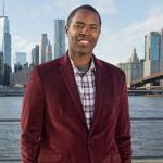 A waist up view of Charlie Ward as he stands in front of a city skyline