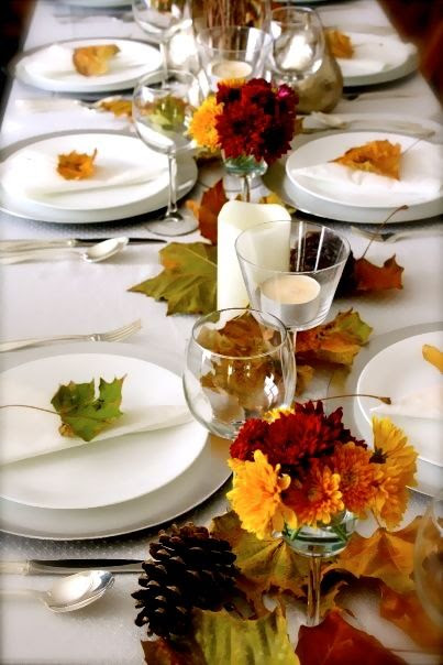 """Small vases of inexpensive seasonal flowers are lined up with foraged leaves to create a """"runner."""""""