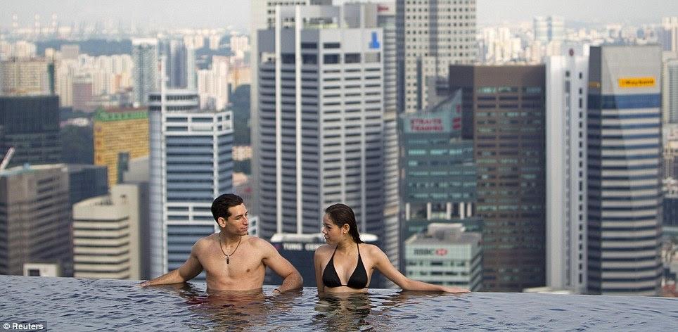 Simplemente disfrutar del sol: Modelos posan en la piscina para los periodistas en la inauguración yesterda