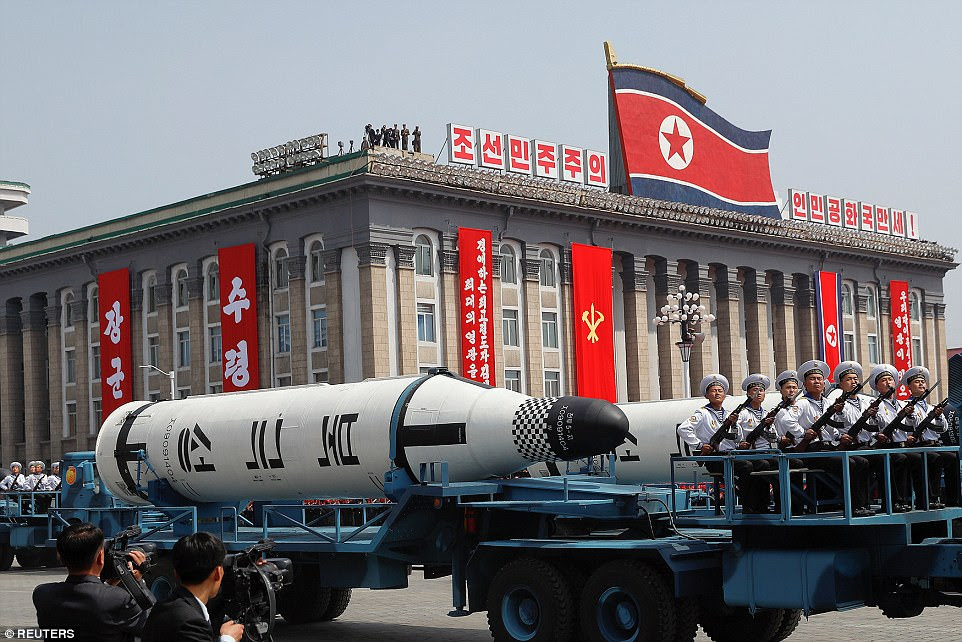 Military vehicles carry missiles during a military parade in North Korean capital Pyongyang today