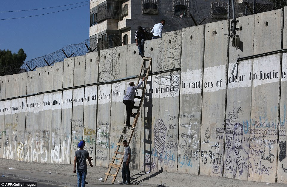 Symbol of aggression: Palestinians climb over a section of Israel's separation wall near Qalandia checkpoint between Ramallah to enter Jerusalem for Friday prayer in the al-Aqsa mosque compound, Islam's third-holiest site, during the holy month of Ramadan last month