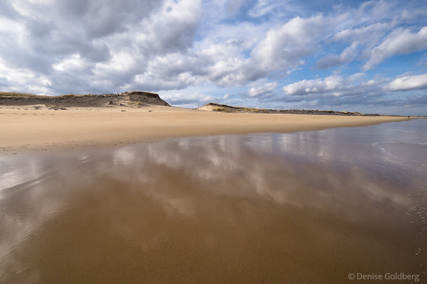 clouds reflect on wet sand, at the Parker River National Wildlife Refuge