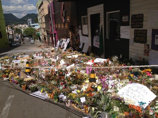 Flores e cartazes em homenagem às vítimas em frente ao prédio onde funcionava a boate Kiss (Foto: Iara Lemos/G1)