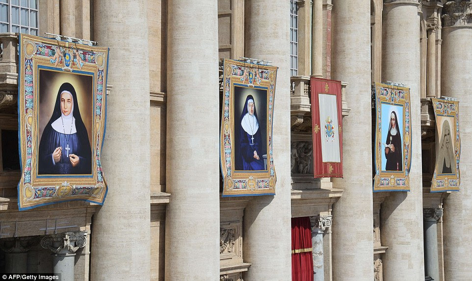 Tapestries depicting the four new saints hang from the facade of St Peter's basilica during today's Papal mass