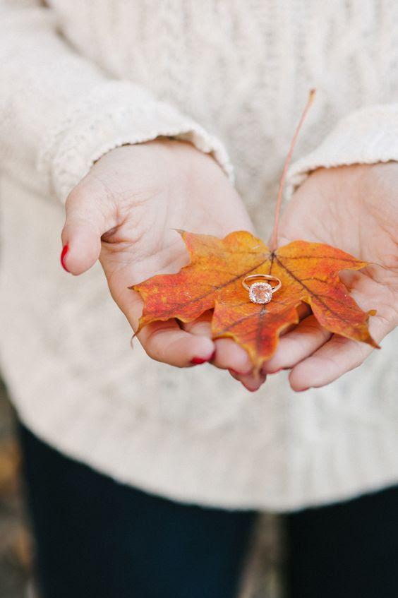 zeigen Sie Ihre Verlobungsring auf einen bunten Herbst-Blatt
