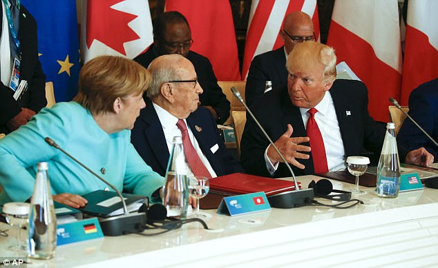 Trump talks to German Chancellor Angela Merkel, left, and Tunisia's President Beji Caid Essebsi, second from left, at a G7 Summit expanded session in Taormina on Italy, May 27