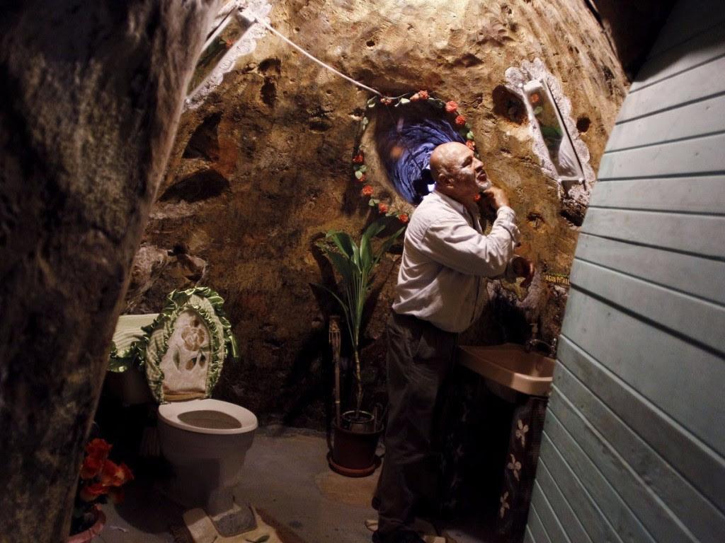 رجل يبنى منزل تحت الارض بعيدًأ عن التلوث الضوضائي