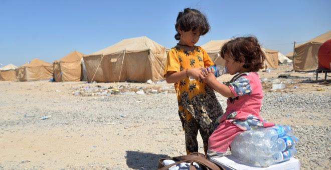 Niños iraquíes migrantes desde Siria reciben suministros de ayuda en un campamento de refugiados en Baiji, al norte de Bagdad. REUTERS/Stringer