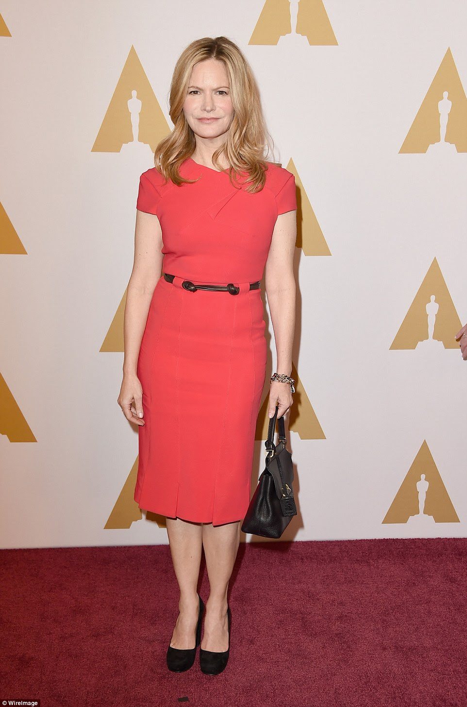 So ladylike: Jennifer Jason Leigh wore a coral colored dress with black pumps and purse - she is nominated for Hateful Eight