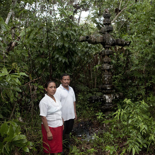 Manuel Alvarado and Carmen Vargas stand beside an oil tap in their backyard.