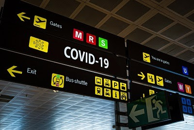 Information panel with Covid-19 word on it at an international airport