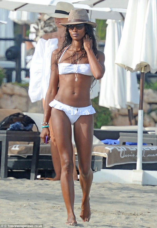Swimwear chic: The British beauty teamed her chic swimwear with a set of simple gold pendants, while sensibly protecting her head from the Spanish sun with the addition of a brown straw fedora
