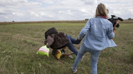 Video journalist fired after apparently kicking, tripping refugees in Hungary