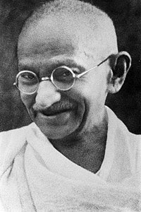 The face of Gandhi in old age—smiling, wearing glasses, and with a white sash over his right shoulder