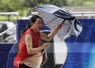A woman walks with her umbrella against strong winds as Typhoon Saola approaches Taiwan in Taipei August 1, 2012. REUTERS/Pichi Chuang