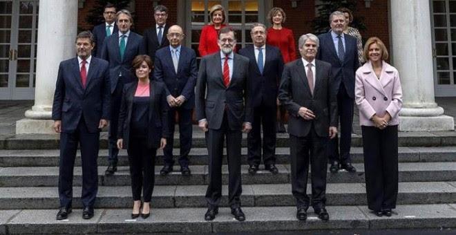 El jefe del ejecutivo, Mariano Rajoy, durante la foto oficial de su nuevo Ejecutivo tras la incorporación de Román Escolano, arriba a la izquierda. | EMILIO NARANJO (EFE)