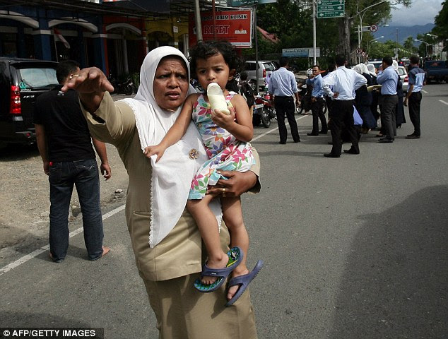 Concern: An Acehnese woman with a child tries to stop a car to go to higher ground after tremors are felt