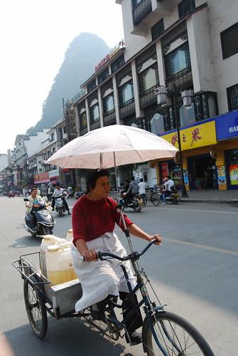 chinesische Frau mit Sonnenschirm auf einem Fahrrad, dahinter Motorräder auf einer Strasse in Yangshou