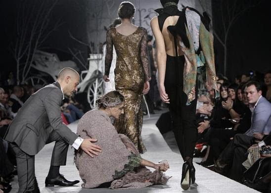 A model is helped by a spectator after she fell while presenting a creation by Georgian designer Irakli Nasidze during Georgian Fashion Week in Tbilisi, Georgia, March 26, 2010. REUTERS-David Mdzinarishvili