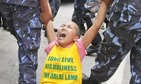 Nepalese police detain a Tibetan protester near the Chinese consulate in Katmandu