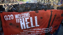 """HAMBURG, GERMANY - JULY 06:  Protesters  dressed in all black hold up a banner as they take part in the """"Welcome to Hell"""" protest march on July 6, 2017 in Hamburg, Germany.  Leaders of the G20 group of nations are arriving in Hamburg today for the July 7-8 economic summit and authorities are bracing for large-scale and disruptive protest efforts tonight at the """"Welcome to Hell"""" anti-G20 protest.  (Photo by Leon Neal/Getty Images)"""