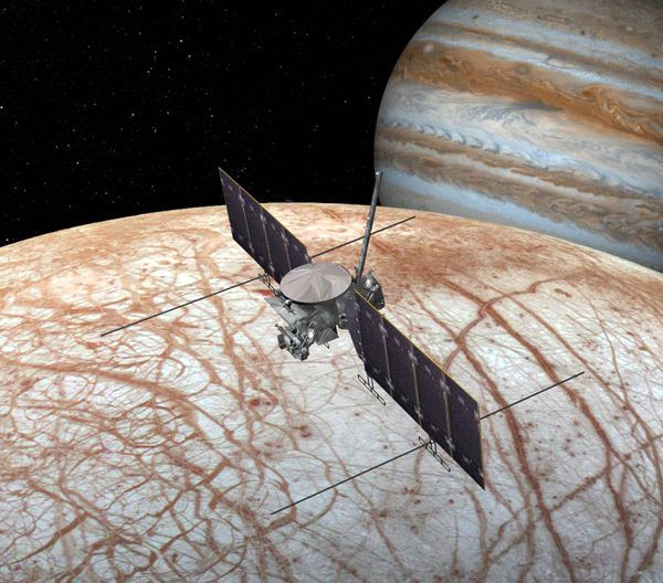 An artist's concept of NASA's Europa Clipper spacecraft flying above Jupiter's icy moon Europa.