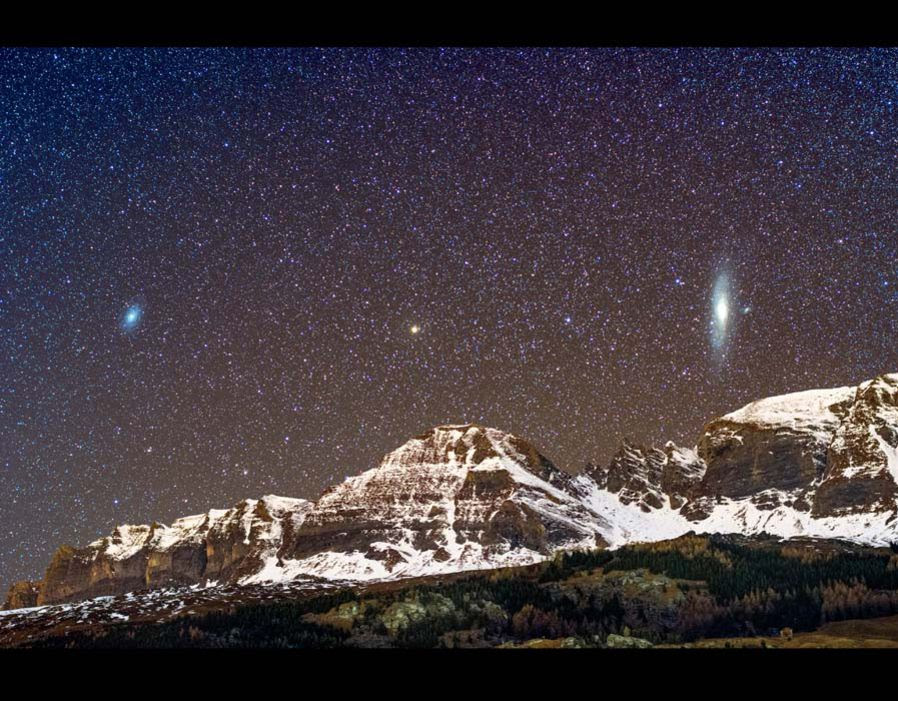A view of the Triangulaum and the Andromeda Galaxy above a mountain