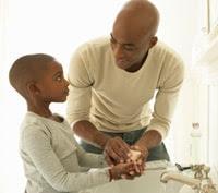 Un hombre lavando las manos de su hijo