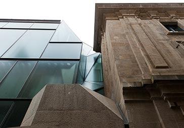 La continuidad entre el nuevo plano de fachada de vidrio y la fachada existente se resuelve mediante un repliegue del plano de vidrio, que, funcionando como canal de desagüe de la cubierta, culmina en el lucernario de la escalera principal.