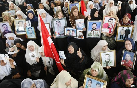 Palestinian women hold photos of relatives held in Israeli prisons as they call for their release.