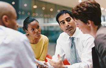 Group of four people in a meeting.