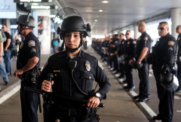 Des policiers surveillent des gens qui manifestent contre... (REUTERS)