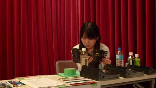 Tsunaoka reading the brochure