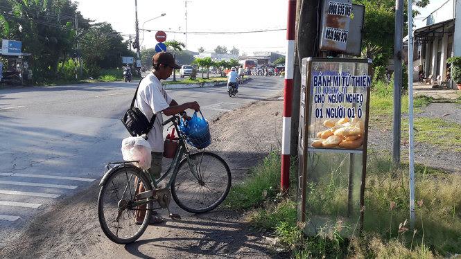 Một người bán vé số đã ghé lại rất sớm để lấy bánh mì lót dạ trong khi đi bán. (Hình: Báo Tuổi Trẻ)
