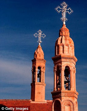 The twin spires of the Mor Gabriel monastery stand against a blue sky