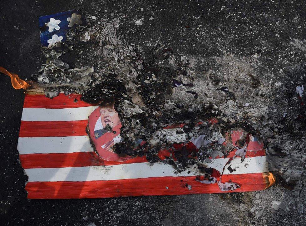 Un grupo de activistas quema una bandera estadounidense durante una manifestación contra la llegada de Donald Trump a la Casa Blanca, frente a la embajada de Estados Unidos en Manila (Filipinas).