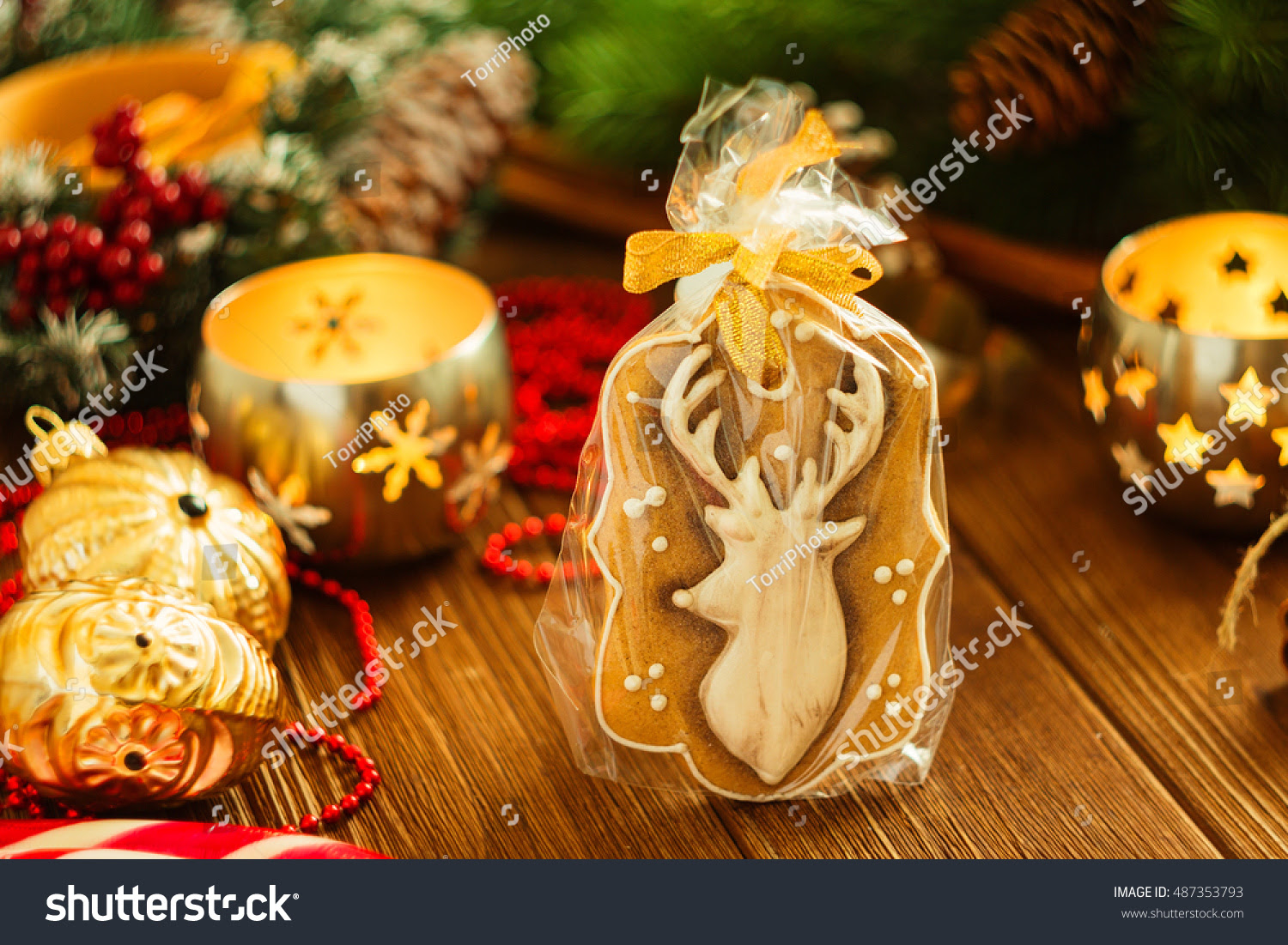 Christmas gingerbread cookies deer on rustic background with Christmas decorations and candle