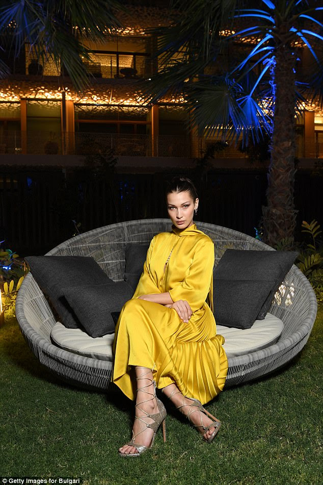 Take a seat: The sweeping frock billowed down to her ankles to reveal a golden pair of heels that laced up to her calves